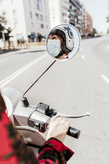 Reflection of woman wearing mask in side-view mirror