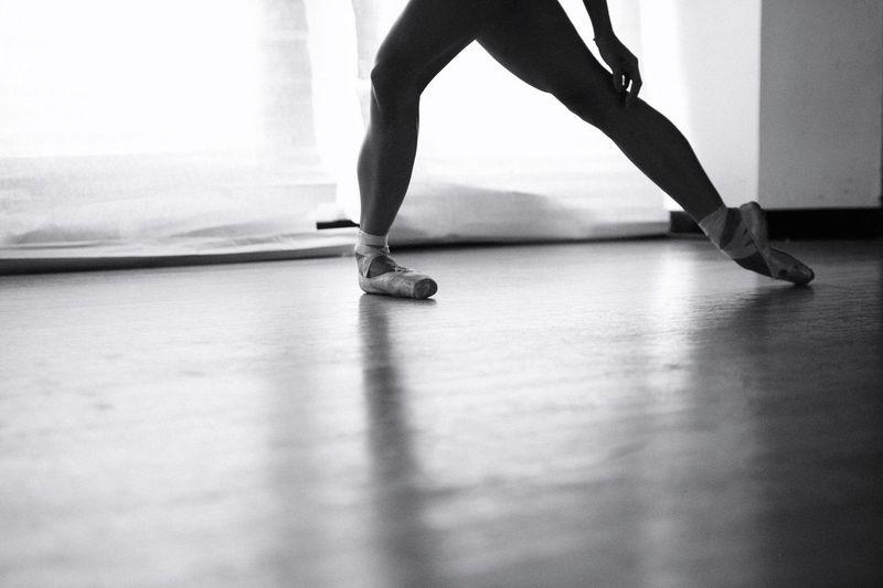 Low Section Of Ballet Dancer Dancing On Hardwood Floor