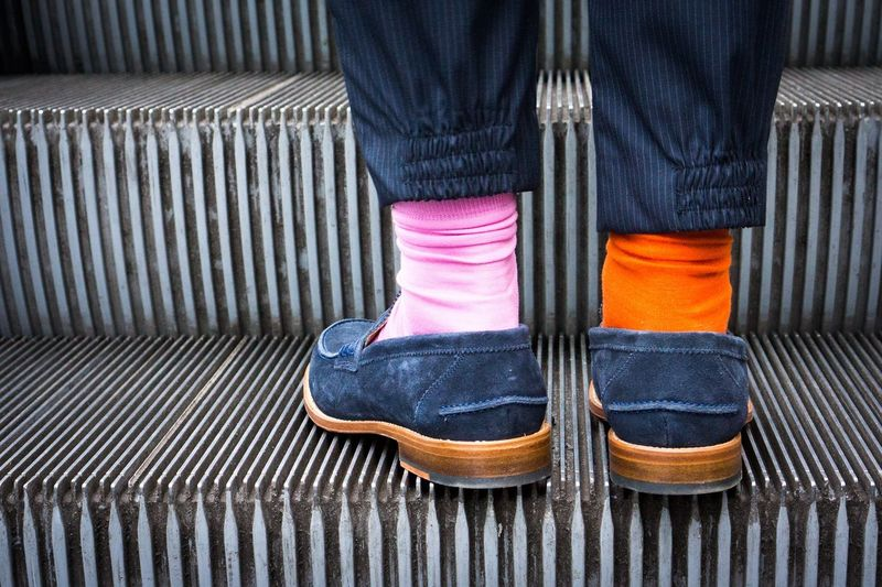 Midsection Of A Person Wearing Two Different Socks On Escalator