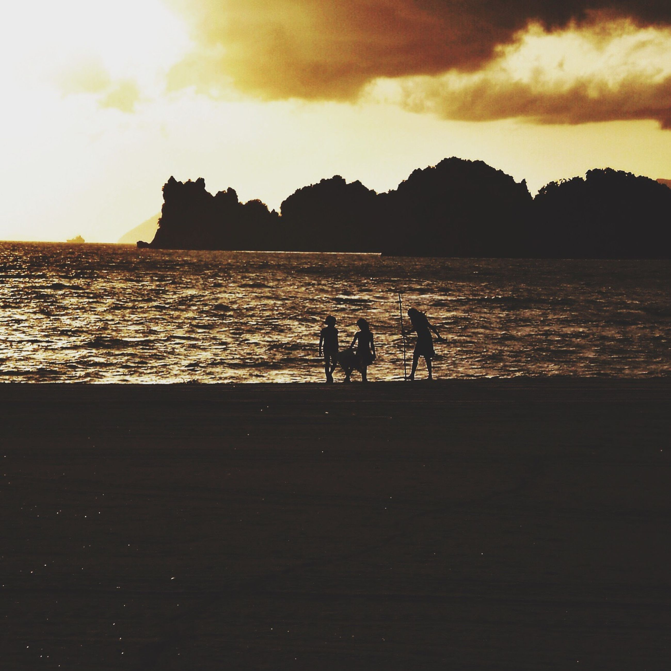 water, silhouette, sunset, sky, leisure activity, lifestyles, sea, men, togetherness, person, cloud - sky, bonding, scenics, beauty in nature, nature, mountain, tranquil scene, tranquility