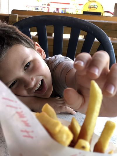 Close-up of boy holding french fries in restaurant