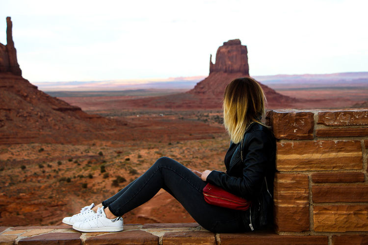Sitting One Person Real People Leisure Activity Lifestyles Full Length Women Sky Casual Clothing Side View Relaxation Mountain Young Adult Nature Adult Hair Environment Beauty In Nature Day Hairstyle Outdoors Monument Valley,Utah USA Monument Valley