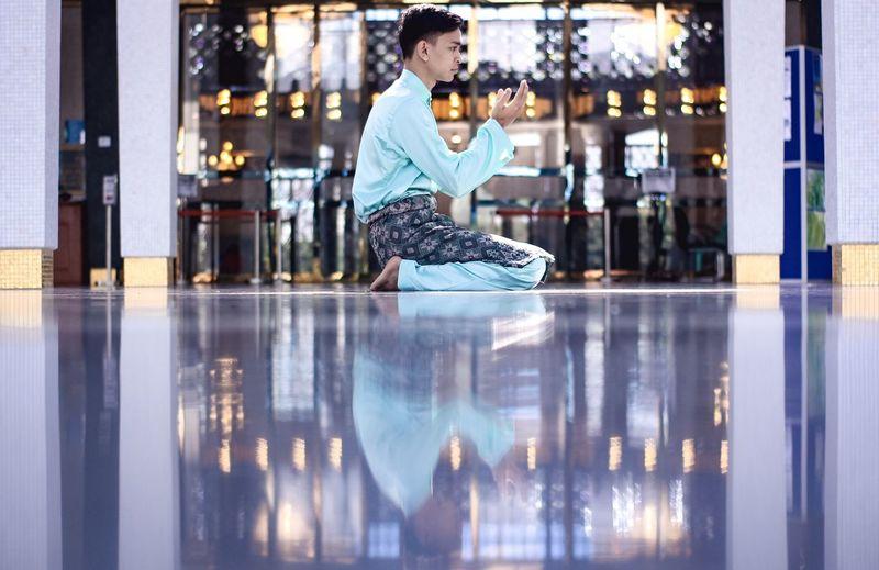 Man praying while sitting on floor