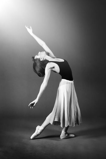 Full length of woman dancing against gray background