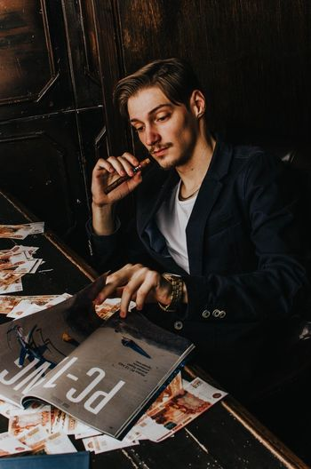 Portrait of young man holding camera on table