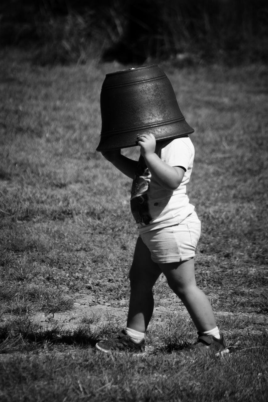 Full Length View Of Boy With Bucket On Head