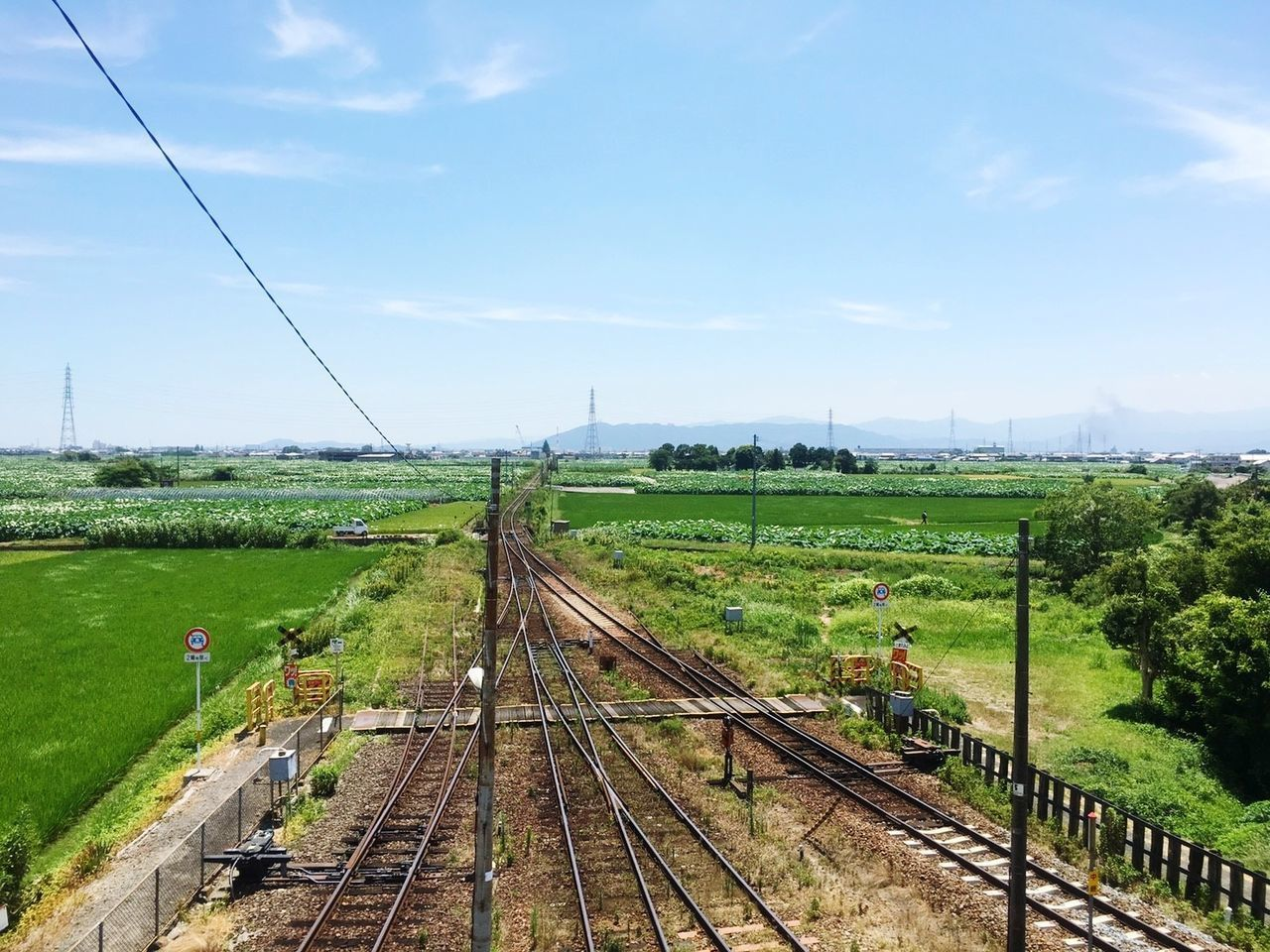 railroad track, rail transportation, transportation, high angle view, sky, day, landscape, scenics, tranquil scene, no people, public transportation, cable, field, tree, outdoors, nature, railway track, train - vehicle, grass, green color, tranquility, beauty in nature