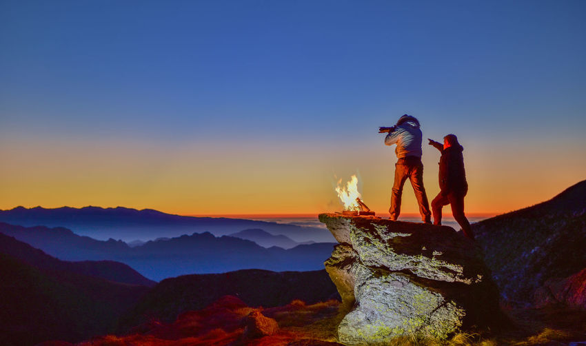Man on mountain against clear sky during sunset
