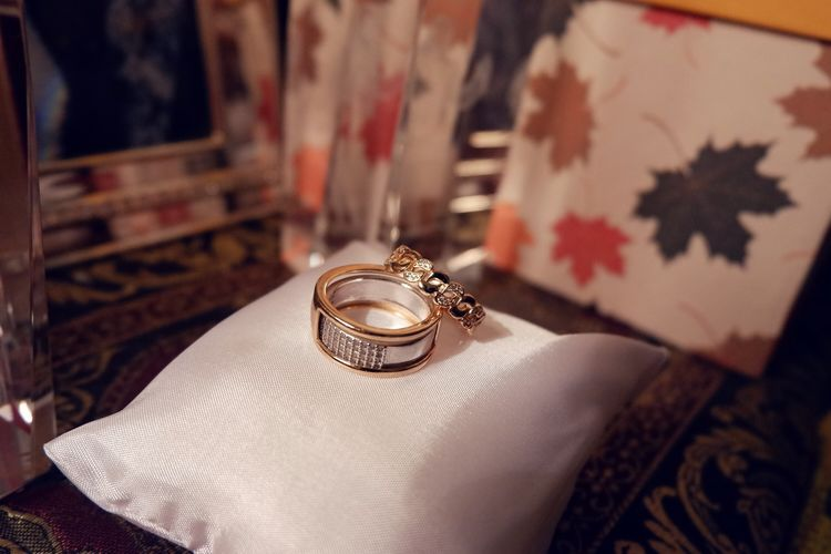 Close-up of wedding rings on pillow