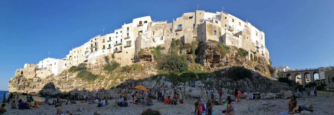 Foto panoramica del centro storico dalla spiaggia di Cala Monachile Cala Monachile Mare Architecture Blue Building Exterior Built Structure Centro Storico City Clear Sky Crowd Day Group Of People History Large Group Of People Nature Outdoors Real People Sky Spiaggia Strapiombo The Past Tourism Travel Travel Destinations Women