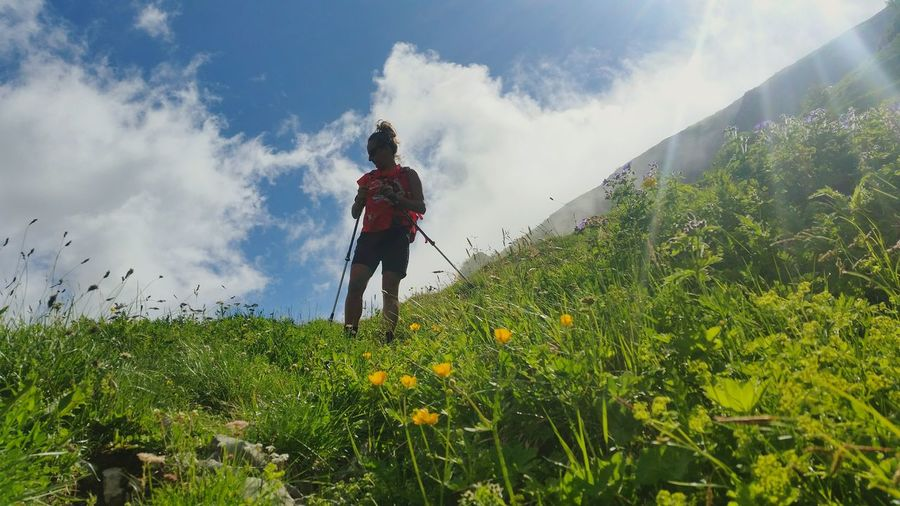 Low angle view of hiker standing on hill during sunny day