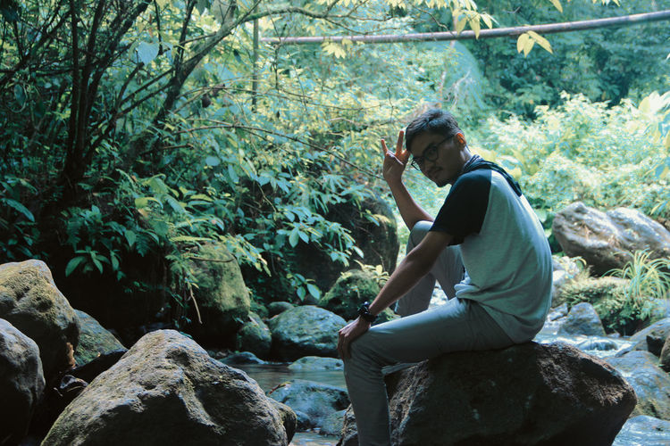 Side View Portrait Of Man Sitting On Rock In Forest