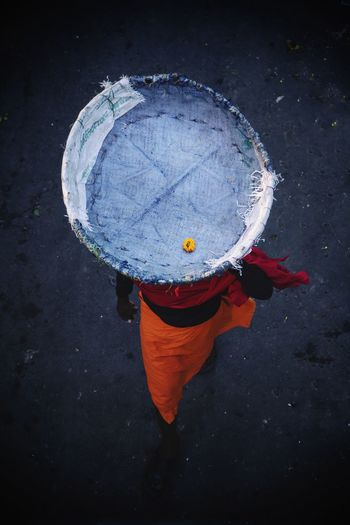 High angle view of man walking with flower in basket on head