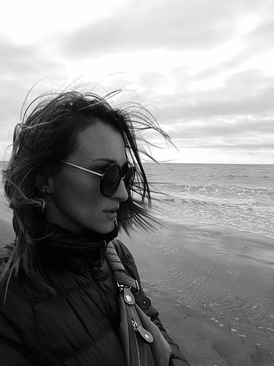 Woman Wearing Sunglasses At Beach Against Sky