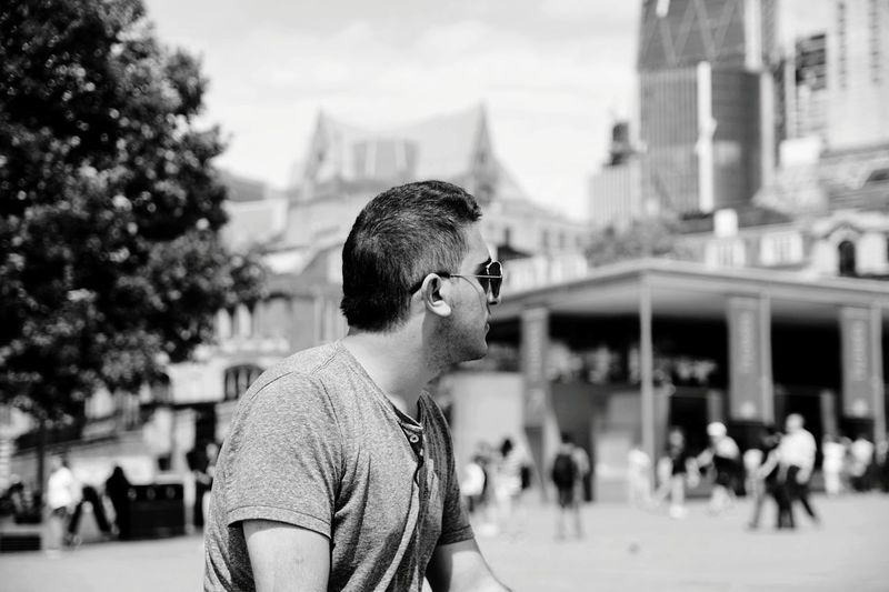 Man wearing sunglasses looking away during sunny day in city