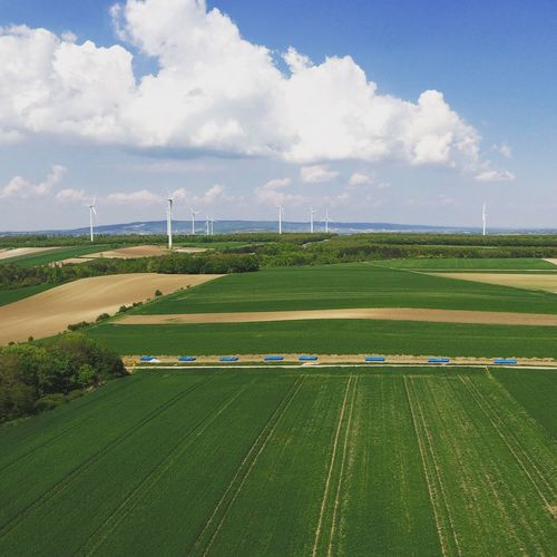 High Angle View Of Agricultural Fields Against Cloudy Sky