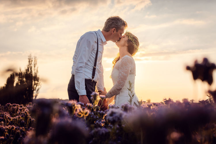 Couple kissing in farm against sky during sunset