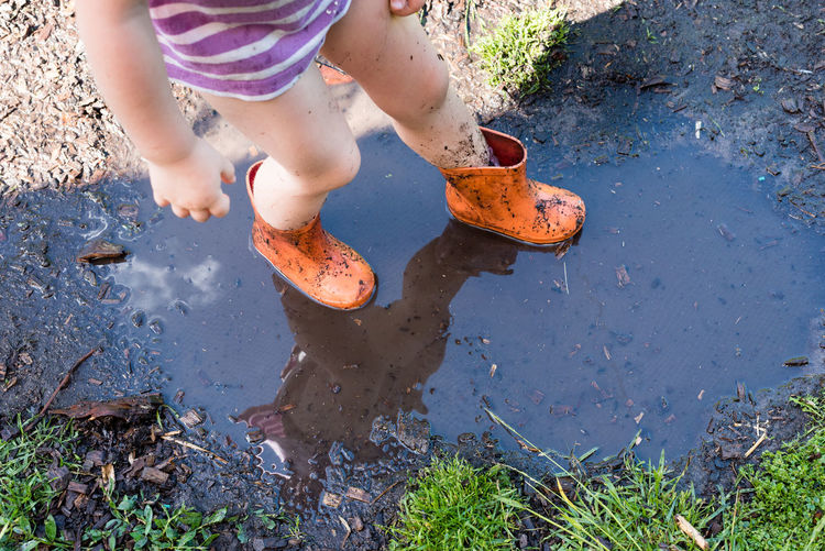 Low Section Of Girl Standing In Puddle On Ground