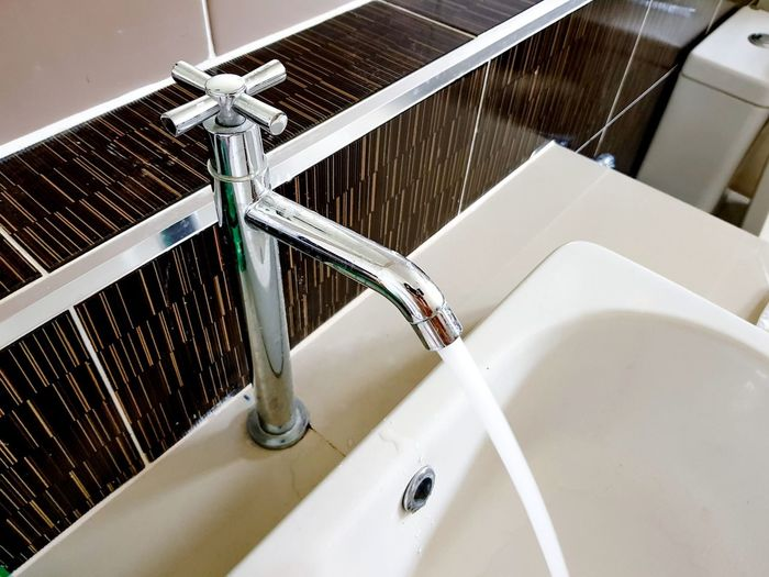 High angle view of water flowing from faucet in sink