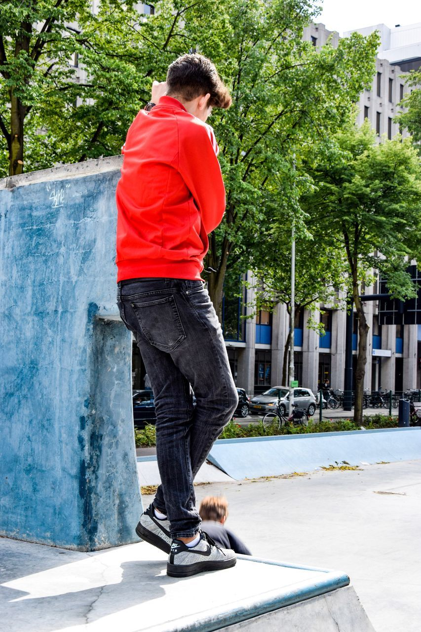 one person, tree, real people, day, outdoors, casual clothing, full length, leisure activity, built structure, building exterior, city, lifestyles, men, architecture, one man only, standing, young adult, skateboard park, nature, only men, adult, people, adults only