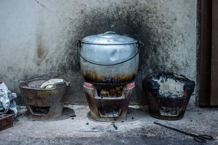 Basic asian cooking stove keeps a metal pot of food hot. Abandoned Charcoal Close-up Cooking Cooking Pot Day Heating Hot Coals Indoors  Keeping Warm Metal Metal Pot No People Outdoors Restaurant Rusty Stove Street Cooking Street Food Tongs Unattended