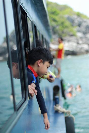 Boy peeking from boat window in sea
