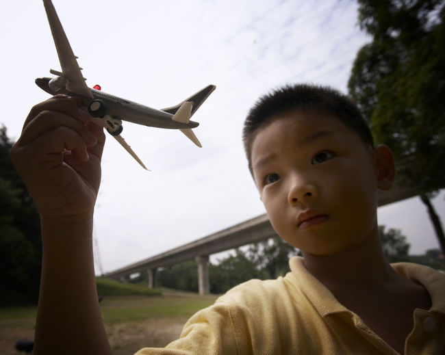 Boy playing with model airplane at park
