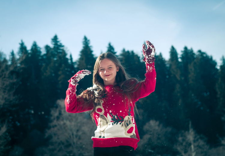 Smiling girl throwing snow while standing outdoors