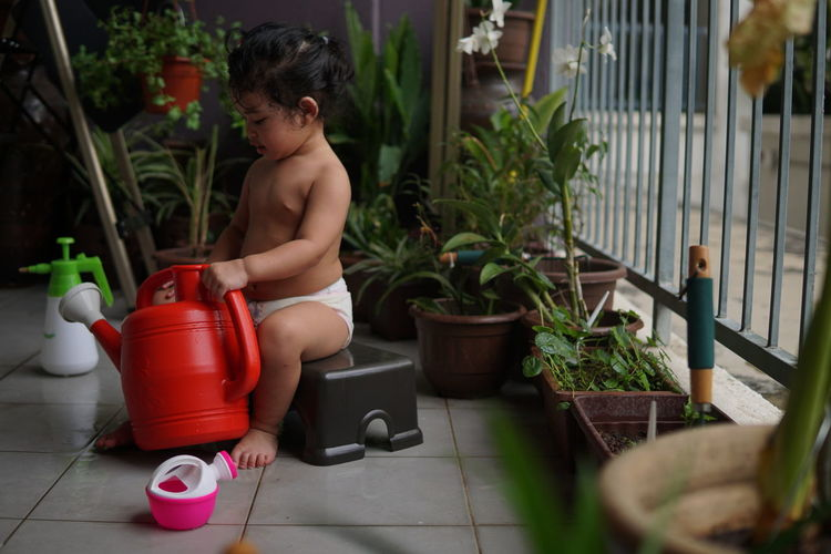 Midsection of shirtless man sitting in potted plants