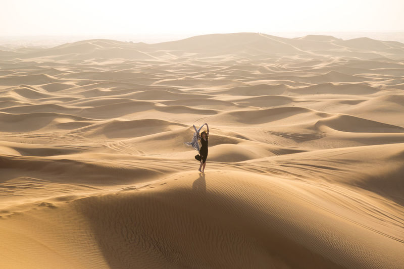 Full length of woman standing on sand dune in desert