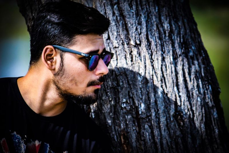 Close-up portrait of young man wearing sunglasses against tree trunk