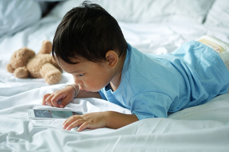 Side view of baby boy using smart phone while lying on bed