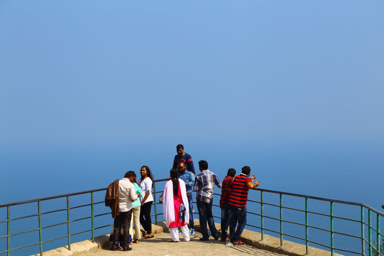 real people, railing, sea, men, water, women, copy space, clear sky, rear view, leisure activity, standing, nature, outdoors, lifestyles, sky, horizon over water, day, large group of people, blue, beauty in nature, vacations, people