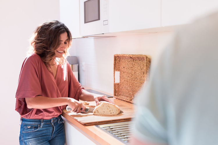 Woman standing on cutting board at home
