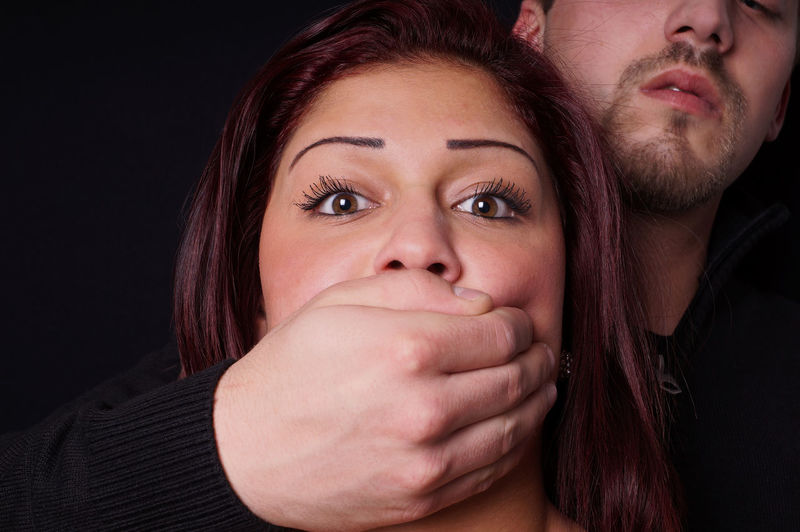 Young Man Covering Woman Mouth With Hand Against Black Background