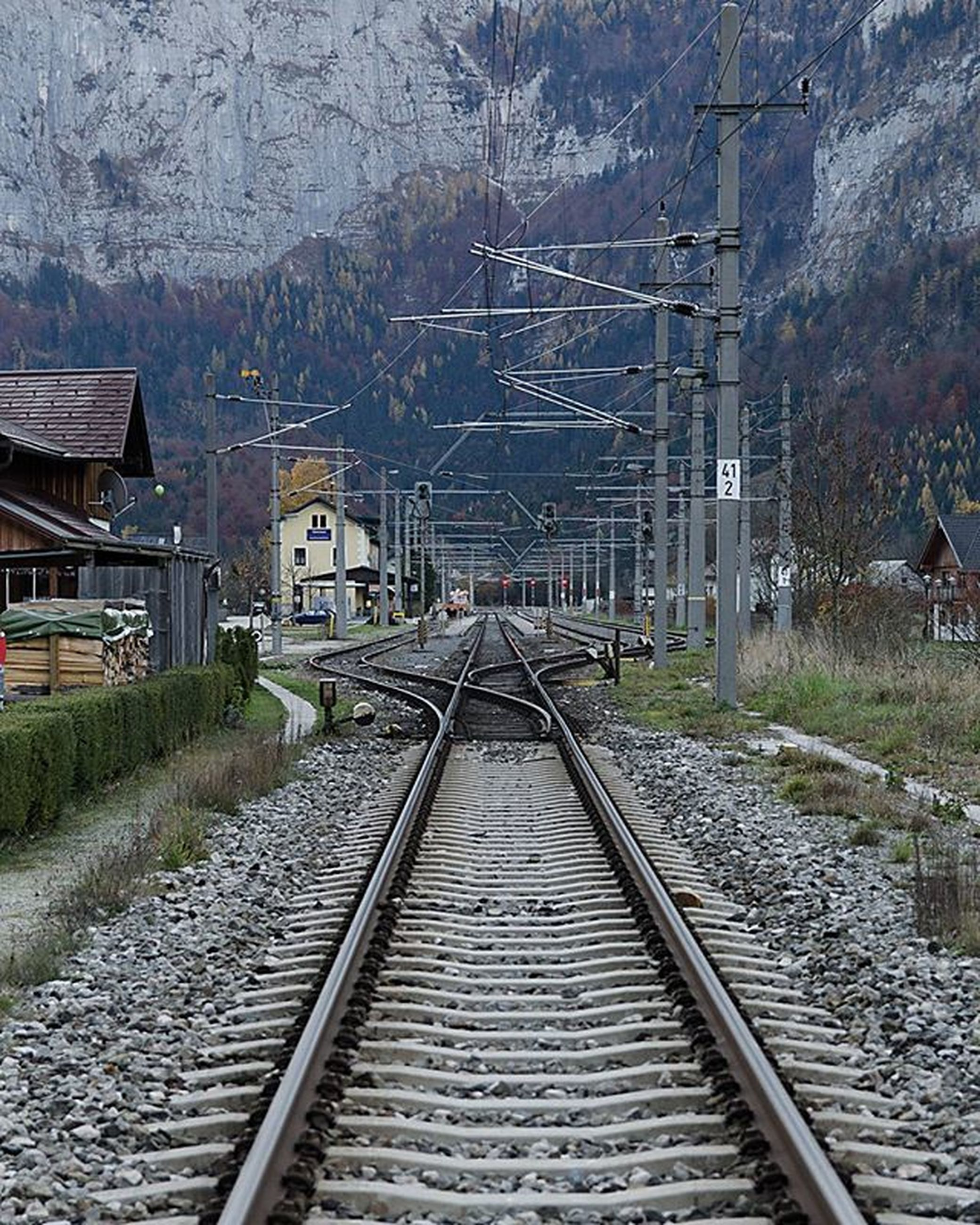 railroad track, rail transportation, building exterior, architecture, built structure, transportation, public transportation, the way forward, train - vehicle, railroad station, diminishing perspective, railway track, railroad station platform, high angle view, day, vanishing point, tree, sky, outdoors, no people