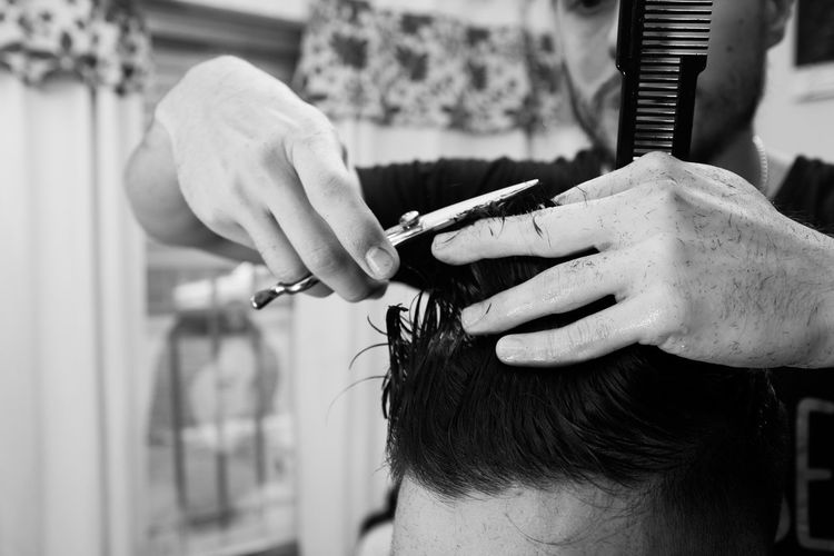 Barber cutting hair of man in the barber shop