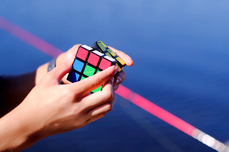 Close-up of hands playing with puzzle cube