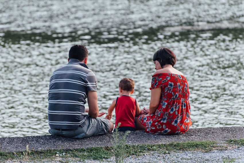 Family Love Mother Mother And Son Adult Bonding Boys Childhood Day Father Father & Son Father And Son Lake Leisure Activity Men Outdoors People Playing Real People Rear View Sitting Togetherness Water Women Family With One Child