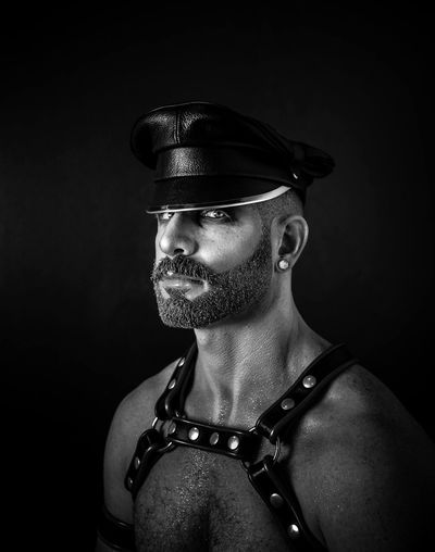 Portrait of man wearing leather harness against black background