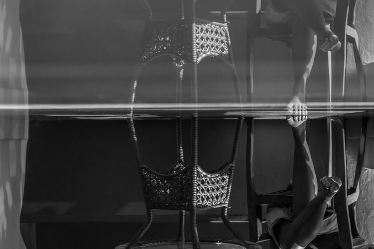 Upside down image of person sitting in chair with reflection on glass