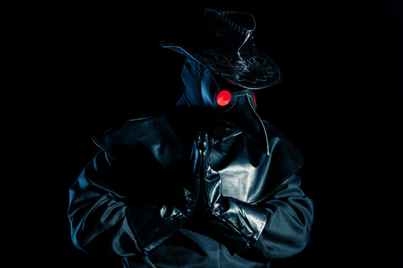 Midsection of man wearing mask against black background