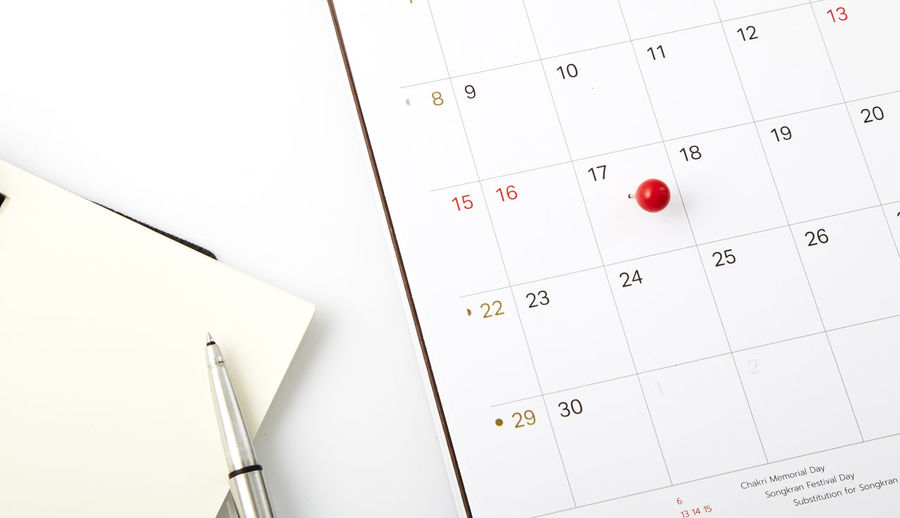 Close-up of diary with pen and thumbtack pinned calendar on table