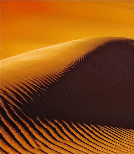 Scenic view of desert against orange sky