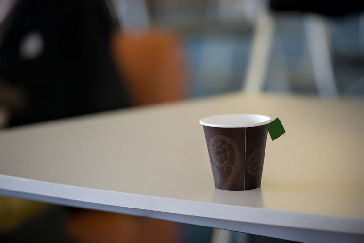Tea in disposable cup on table