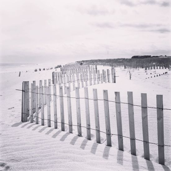 View Of Fence On Beach Against Cloudy Sky