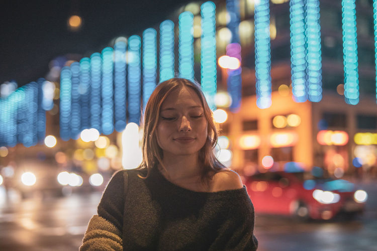 Fashionable Young Woman In City At Night