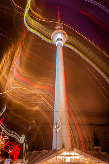 Low angle view of light trails by fernsehturm against sky