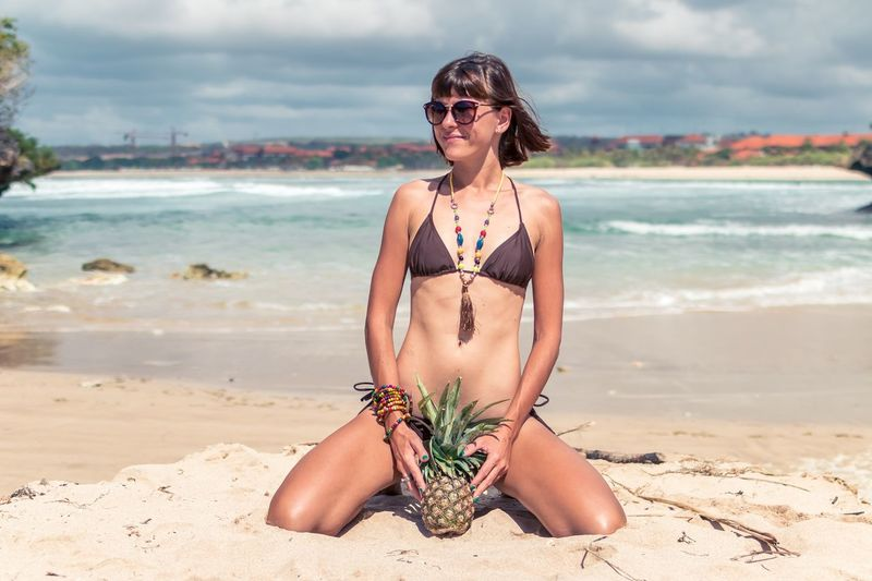 Full length of young woman in bikini holding pineapple at beach