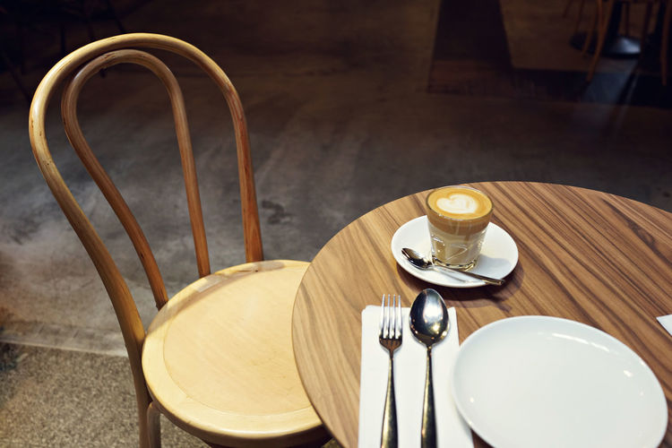 High Angle View Of Coffee On Table By Chair